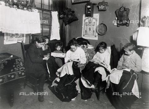 GRC-F-015550-0000 - Immigrati italiani: una donna con i suoi bambini cuciono tessuti per abbigliamento a New York - Data dello scatto: 1905 ca. - Granger, NYC /Archivi Alinari