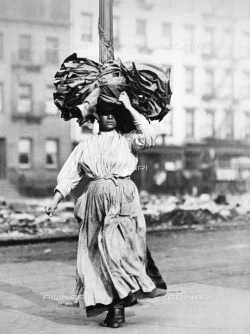 GRC-F-030708-0000 - Donna immigrata italiana che trasporta sulla testa della stoffa, New York, Lower East Side - Data dello scatto: 02/1912 - Granger, NYC /Archivi Alinari