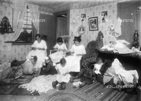 GRC-F-038399-0000 - Immigrati italiani: una donna con ragazze e bambini cuciono tessuti per abbigliamento - Data dello scatto: 1910 ca. - Granger, NYC /Archivi Alinari