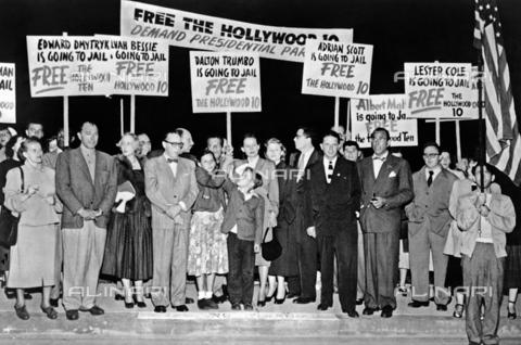 GRC-F-526935-0000 - Lo sceneggiatore americano Dalton Trumbo (1905-1976), secondo uomo da sinistra, circondato dai sostenitori, mentre si dirige verso la prigione per scontare una condanna di un anno per disprezzo del Congresso e per essersi rifiutato di fornire informazioni sul Comunismo a Hollywood - Data dello scatto: 1950 - Granger, NYC /Archivi Alinari
