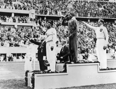 GRC-F-635697-0000 - Gli atleti di atletica leggera Jesse Owens, Lutz Long e Naoto Tajima, sul podio durante la cerimonia di premiazione per il salto in lungo alle Olimpiadi del 1936 a Berlino - Data dello scatto: 1936 - Granger, NYC /Archivi Alinari