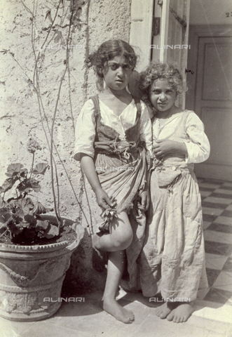 GWA-F-000644-0000 - Full-length portrait of two small working class girls in umili clothes. The small girls, without shoes, are posing l'una vicina all'altra on the entrance of a house. The elder has a lembo of her dress vezzosamente sollevato to show her legs - Data dello scatto: 1904 ca. - Archivi Alinari, Firenze