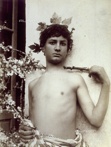 GWA-F-000703-0000 - Artistic photograph of an adolescent dressed as Baccus. The little boy is posing a nude, against a wall, and his head has a crown of vine leaves - Data dello scatto: 1900 ca. - Archivi Alinari, Firenze