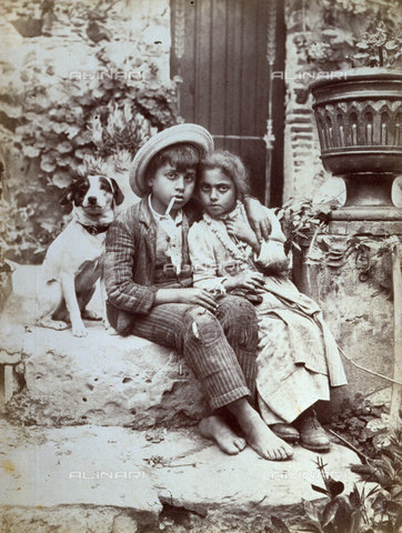 GWA-F-000711-0000 - Full-length portrait of two small working class children in poor clothes. The children, with sad and serious expression, are sitting on a stone step, tenderly embrassed each other. Behind them a small dog - Data dello scatto: 1895-1903 ca. - Archivi Alinari, Firenze