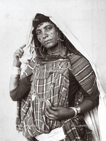 GWA-F-000734-0000 - Three-quarter-length portrait of a young Berber woman in ethnic clothes, with a long scialle on her head. The woman, adorned with vistosi jewels, is posing showing her tatuato face - Data dello scatto: 1890 ca. - Archivi Alinari, Firenze