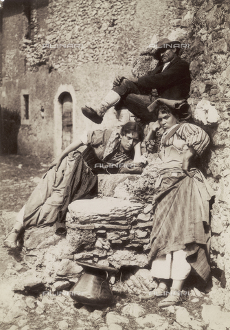 GWA-F-000756-0000 - Two young working class women and a man in traditional clothes are posing against a small stone wall in a sunny street of the old Taormina, Italy - Data dello scatto: 1895-1905 ca. - Archivi Alinari, Firenze