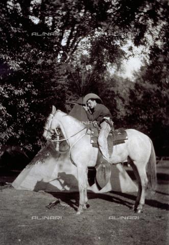 GWA-F-000788-0000 - Portrait, in profile, of a young boy dressed as cow-boy, on a horse in a radura boschiva. L'effigiato imbraccia un fucile simulando un attacco verso un probabile avversario. Behind him an Indian tent can be seen - Data dello scatto: 1900-1910 ca. - Archivi Alinari, Firenze