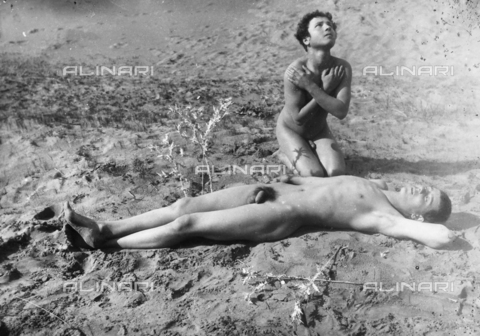 GWN-F-000482-0000 - Reenactment of a mythological scene: a nude man lies in the sand with an adolescent kneeling next to him - Data dello scatto: 1895 - 1905 - Archivi Alinari, Firenze