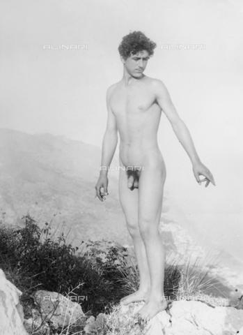 GWN-F-003026-0000 - A young man poses nude standing on a rock - Data dello scatto: 1895 - 1905 - Archivi Alinari, Firenze