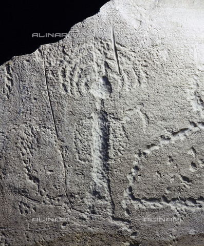 HIP-S-000233-0339 - Rock engraving depicting a warrior with a feathered headdress, Plains Indian, from the Bighorn Basin, Wyoming, USA. Rock art was produced over a period of at least 3000 years until the disruptive effects of European conquest. As yet satisfactory dating of specific sites has rarely been possible. From the Plains Indian Museum, Buffalo Bill Historical Center, Cody, Wyoming - Werner Forman Archive / Heritage Images /Alinari Archives, Florence