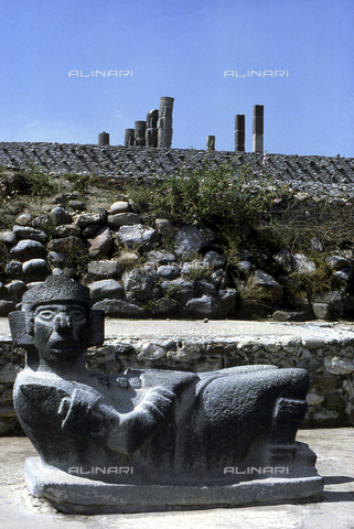 HIP-S-000235-6974 - Toltec Chac Mool sculpture, Tula, Mexico, 950-1150. In the distance are the Pyramid of Quetzalcoatl and Atlantid statues. For the Toltecs the Chac Mool represents the divine messenger who received and carried to the Sun the offering of human sacrifice - Heritage Images /Alinari Archives, Florence, Werner Forman Archive/ N.J.Saunders