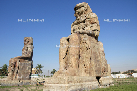 HIP-S-000236-7511 - The Colossi of Memnon, Luxor (Thebes), Egypt.The twin statues depict the Pharaoh Amenhotep III and stood in front of his mortuary temple, which has been destroyed. Amenhotep was the 9th Pharaoh of the 18th dynasty of Ancient Egypt. He ruled from 1391-1353 BC. The two shorter figures by Amenhotep's legs are his wife, Tiy and mother, Mutemwiya - Heritage Images /Alinari Archives, Florence, Werner Forman Archive/ N.J Saunders