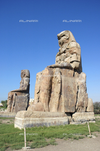 HIP-S-000236-7512 - The Colossi of Memnon, Luxor (Thebes), Egypt. The twin statues depict the Pharaoh Amenhotep III and stood in front of his mortuary temple, which has been destroyed. Amenhotep was the 9th Pharaoh of the 18th dynasty of Ancient Egypt. He ruled from 1391-1353 BC. The two shorter figures by Amenhotep's legs are his wife, Tiy and mother, Mutemwiya - Heritage Images /Alinari Archives, Florence, Werner Forman Archive/ N.J Saunders