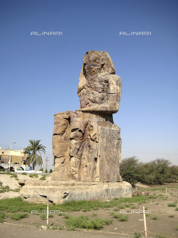 HIP-S-000236-7513 - One of the Colossi of Memnon, Luxor (Thebes), Egypt. The twin statues depict the Pharaoh Amenhotep III and stood in front of his mortuary temple, which has been destroyed. Amenhotep was the 9th Pharaoh of the 18th dynasty of Ancient Egypt. He ruled from 1391-1353 BC - Heritage Images /Alinari Archives, Florence, Werner Forman Archive/ N.J Saunders