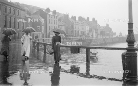 HIP-S-000266-7880 - A rainy day on Pier Road, Whitby, North Yorkshire, 1896-1920. People with raincoats and umbrellas walking beside the harbour in the rain - Historic England Archive / Heritage Images /Alinari Archives, Florence