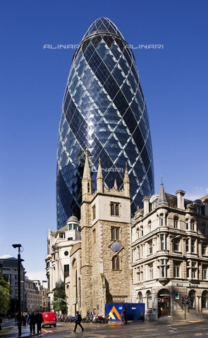 HIP-S-000266-7887 - Church of St Andrew Undershaft and the Gherkin, City of London, 2012. The 1894 London Building Act restricted the height of buildings until these regulations were relaxed in the 1950s and the boom in tall buildings began. The tower of the church of St Andrew Undershaft dates from the 15th century, and for centuries it dominated buildings in Leadenhall Street, particularly after the addition of corner pinnacles and a turret in 1883. Many buildings beyond the church were destroyed by fire in 1893, and replaced by the Baltic Mercantile amp; Shipping Exchange and other commercial buildings. The Baltic Exchange was badly damaged by an IRA bomb in 1992, and made way for 30 St Mary Axe, popularly known as the Gherkin, which was designed by Foster and Partners and completed in 2004 - Data dello scatto: 2012 - Historic England Archive / Heritage Images /Alinari Archives, Florence