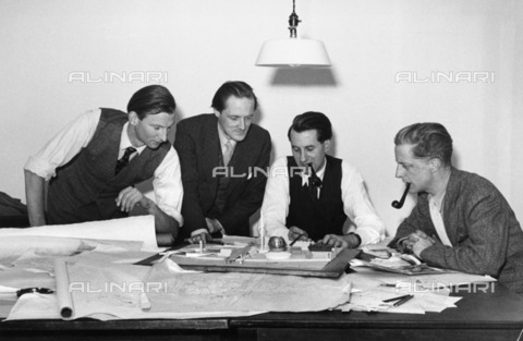 HIP-S-000266-7911 - Architects and designers discussing the plans for the Festival of Britain, 1949. Ralph Tubbs, Hugh Casson, James Holland and James Gardner discussing plans and models of the Central Exhibition of the festival - Data dello scatto: 1949 - Historic England Archive / Heritage Images /Alinari Archives, Florence