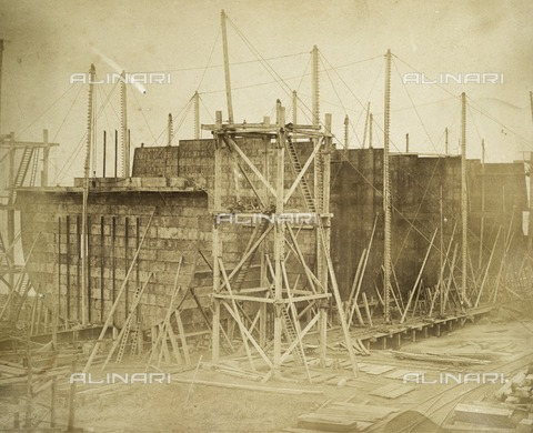 HIP-S-000266-7912 - The 'Great Eastern' under construction, Millwall, London, 1855. Albumen print. Isambard Kingdom Brunel's steamship 'Great Eastern', built between 1854 and 1858, was by far the largest ship of her time with a gross tonnage of 18,915. Designed to carry up to 4000 passengers between England, the Far East and Australia without refuelling, Great Eastern was the first ship to have a double-skinned hull. The construction of the vessel at Millwall attracted huge public interest, and it was famously photographed by Robert Howlett as well as by Joseph Cundall. Despite acute financial difficulties, and failed launches in November 1857, Great Eastern was eventually launched in January 1858 - Data dello scatto: 1855 - Historic England Archive / Heritage Images /Alinari Archives, Florence