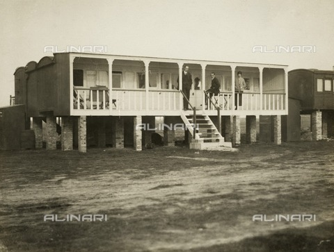 HIP-S-000266-7935 - Railway carriage converted into a holiday home, possibly at Shoreham-by-Sea, West Sussex, 1920s. Silver gelatin DOP (developing out paper) print. Holidaymakers pose on the verandah. Between the wars, the freedom offered by the motor car and ambiguous planning regulations stimulated the creation of plotland developments in remote or undeveloped stretches of coastline and countryside. Shoreham Beach in West Sussex was one such development, and these photographs may have been taken there. Railway carriages, cheap to build shacks and bungalows were built or converted to be both holiday homes and more permanent dwellings. Plotland developments principally catered for the urban working class, but they also attracted artistic and bohemian folk, eager to find places free from conventional restrictions where open skies and dramatic changes in the weather could stimulate artistic creativity - Data dello scatto: 1920 ca. - Historic England Archive / Heritage Images /Alinari Archives, Florence