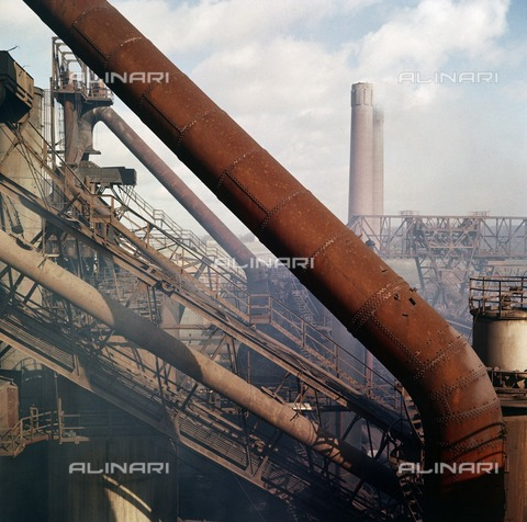 HIP-S-000266-7936 - Consett Steelworks, County Durham, 1945-1980. Cellulose acetate negative. Steel-making dominated Consett for 140 years from 1840, and the steelworks, employing 6000 workers in the 1960s, loomed over rows of terraced houses. Eric de Mare's elevated view of Consett Steel Works captures their gargantuan scale, echoing the work of pre-war photographers such as Albert Renger-Patzsch in Germany and Charles Sheeler in the United States who emphasised the strong forms of industrial structures. De Mare used colour photography here, recognising that this required a 'different vision' from black-and-white film. The massive tube in the foreground reflects his view that a close shot filling or 'well filling' the frame will usually be more effective and more interesting' - Data dello scatto: 1945-1980 - Historic England Archive / Heritage Images /Alinari Archives, Florence