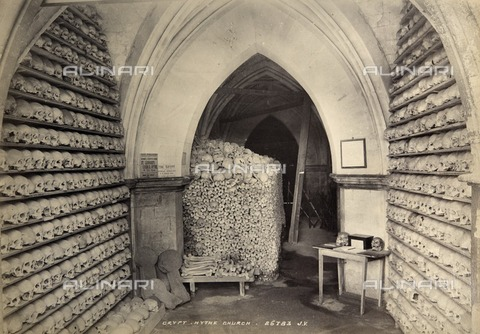 HIP-S-000266-7945 - Crypt, St Leonard's Church, Hythe, Kent, c1900. This image shows the ossuary, or bone store, in the vaulted ambulatory beneath the chancel of the church. The space had been used to store skulls and other bones disturbed during building work or when new graves were dug. Some 10,000 bones, including around 2000 skulls, dating from the medieval period were arranged on shelves or stacked in piles. The ossuary had long attracted visitors, and the photograph shows advertisements for guides written by the vicar, and a table with what appears to be a visitors' book and a donations box. Albumen print - Data dello scatto: 1900 ca. - Historic England Archive / Heritage Images /Alinari Archives, Florence