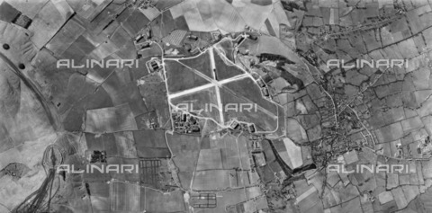 HIP-S-000267-2748 - Wroughton, Wiltshire, 1944. Aerial photograph showing Barbury Castle hillfort, RAF Wroughton (centre), and the village of Wroughton. Wear lines indicate Barbury Castle and the Ridgeway have been used as a thoroughfare by military traffic. There are a number of aircraft in holding areas around the airfield, probably awaiting repairs. Most of the hangars are still extant and now in use by the Science Museum - Data dello scatto: 1944 - Historic England Archive / Heritage Images /Alinari Archives, Florence