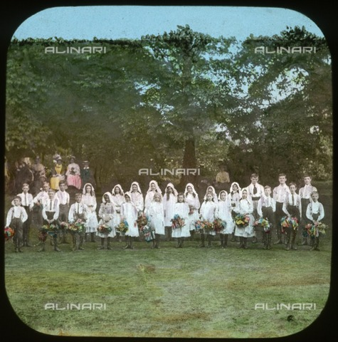 HIP-S-000267-2773 - Strawberry Fair, Iffley, Oxford, Oxfordshire, 1908. A group of local children dressed in May Day costumes, posing for the camera before they start country dancing. Hand-tinted lantern slide - Data dello scatto: 1908 - Historic England Archive / Heritage Images /Alinari Archives, Florence