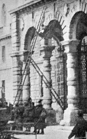 """IIB-S-091847-482C - First World War: the biceps eagle is removed from the facade of the palace of the Austrian Lieutenancy or Palace of the Prefecture of Trieste on October 31st. Photography taken from the magazine """"L' Illustrazione italiana"""" of November 24, 1918, no. 47, page 482C - Date of photography: 31/10/1918 - Library of Fratelli Alinari Museum of the History of Photography, Florence"""