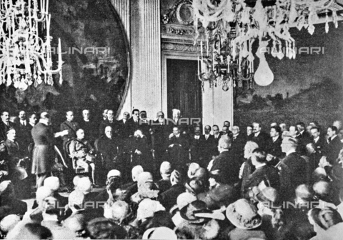 """IIB-S-092218-520A - The art historian Arduino Colasanti (1877-1935) pronounces the speech in the presence of King Vittorio Emanuele II on the occasion of the inauguration of the Italian Painting Exhibition of the seventeenth and eighteenth centuries in the Sala degli Stucchi at Palazzo Pitti. Photography taken from the magazine """"L'Illustration Italian"""" of 30 April 1922, n. 18, page 520 - Date of photography: 20/04/1922 - Library of Fratelli Alinari Museum of the History of Photography, Florence"""