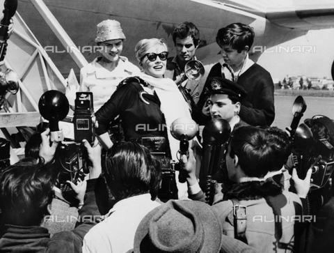 INT-F-201100-0000 - Anita Ekberg scende da un aereo circondata dai giornalisti - Data dello scatto: 1959 - Interfoto/Archivi Alinari
