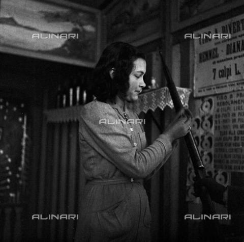 LAA-F-000222-0000 - Istantanea di una giovane ambulante al lavoro in un baraccone da Luna Park adibito al tiro a segno - Data dello scatto: 1935 -1940 ca. - Archivi Alinari, Firenze
