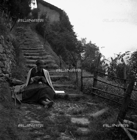 LAA-F-000268-0000 - Alida Valli in a break on the set of the film 'Piccolo Mondo Antico'. She is shown seated on a step in the open countryside, knitting - Data dello scatto: 1940 ca. - Archivi Alinari, Firenze