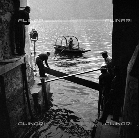 LAA-F-000274-0000 - Electricians and operators at work on the set of the film 'Piccolo Mondo Antico', set up along the banks of the Lake of Como. At the center of the picture, a typical boat moves through the tranquil waters of the lake - Data dello scatto: 1940 ca. - Archivi Alinari, Firenze
