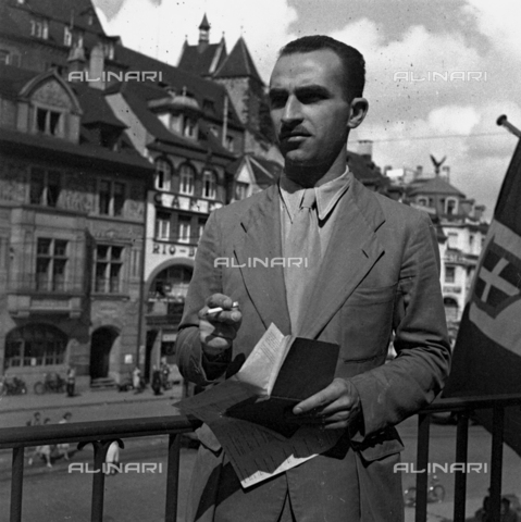 LAA-F-000296-0000 - Three-quarter length portrait of Alberto Lattuada. The famous film director is posing on the balcony of a building, with a cigarette in his right hand and a booklet in his left - Data dello scatto: 1942 -1951 ca. - Archivi Alinari, Firenze