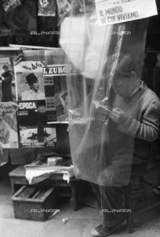 """LFA-F-000086-0000 - """"Il mondo in cui viviamo"""" un bambino che sfoglia un piccolo libro davanti ad un'edicola, Venezia - Data dello scatto: 1950 ca. - Archivi Alinari, Firenze"""