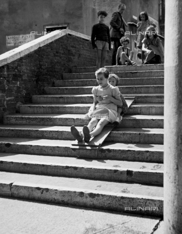 "LFA-F-000090-0000 - St. Barnaba, Venice; Children, slide on the Beccarie Bridge"". A group of children play on the bridge, sliding down the step on a piece of wood"