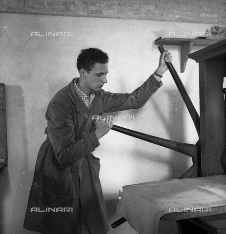 LFA-S-0000O1-0067 - Istituto d'Arte di Venezia: un ragazzo al lavoro nel laboratorio di stampa con un torchio - Data dello scatto: 1945 ca. - Archivi Alinari, Firenze