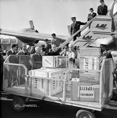 LLA-S-00X293-A003 - Priest blesses at the Ciampino airport the antibiotics of the pharmaceutical company Lepetit destined for Hungary - Data dello scatto: 29/10/1955 - Luigi Leoni Archive / Alinari Archives