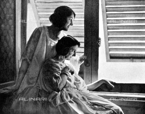 LOB-S-000924-0018 - In un pomeriggio estivo due giovani donne spiano con aria di divertita complicità la strada sottostante attraverso le persiane di una finestra - Data dello scatto: 1923-1924 - Archivi Alinari, Firenze