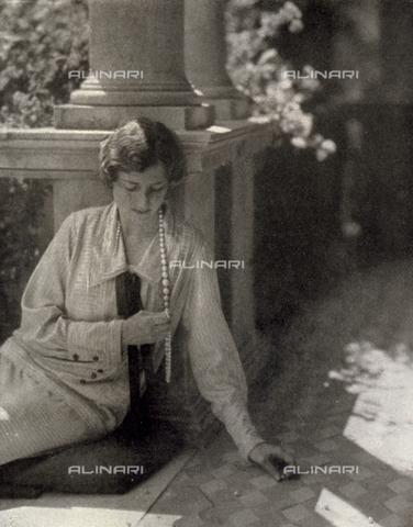 LOB-S-000925-0036 - Ritratto di una giovane signora, vestita con elegante abito tipico degli Anni Venti, seduta sullo scalino del loggiato di un'abitazione signorile e intenta a raccogliere le perle cadute dalla sua collana, sparse sul pavimento a scacchiera - Data dello scatto: 1924-1925 - Archivi Alinari, Firenze