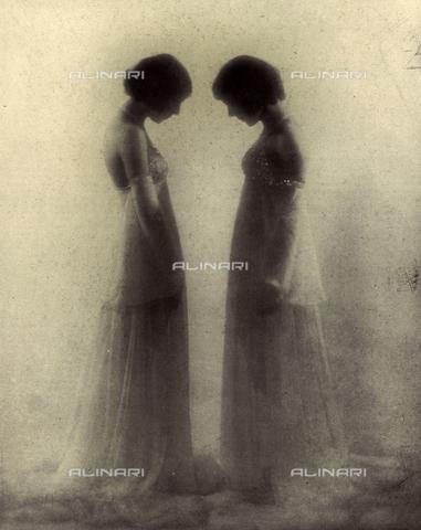 LOB-S-000930-0043 - Ritratto a figura intera, di profilo, di due fanciulle. Le belle e giovani donne, vestite con eleganti abiti da sera bianchi uguali e capelli raccolti, si fronteggiano suggerendo l'impressione di specchiarsi l'una nell'altra. Il chiarore dello sfondo e la sfocatura di intenso effetto pittorico creano un'atmosfera poetica e riflessiva - Data dello scatto: 1929-1930 - Archivi Alinari, Firenze