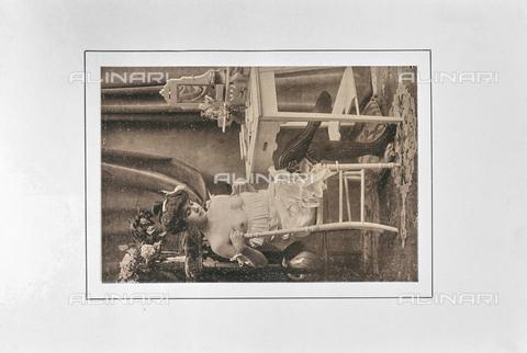 """LVQ-L-000214-P005 - Woman with breast exposed in front of the furniture of the make-up, photography taken from the dossier """"Le Deshabillé documentaire. Etude artistique Illustrée de Cent compositions photographiques d'après Nature"""", 1 Fascicule, J. B. de la Hoà¼e, Nouvelle Librairie Artistique 7-9 Rue de la Boà«tie, Paris - Date of photography: 1900-1910 ca. - Fratelli Alinari Museum Collections, Florence"""