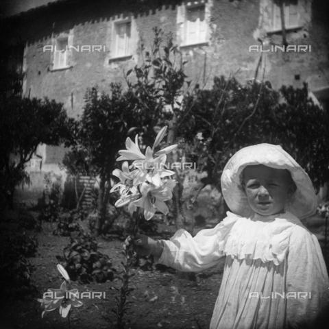 MFA-S-0SN390-000S - Portrait of a child holding some lilies in his hand - Data dello scatto: 1900 ca. - Archivi Alinari, Firenze