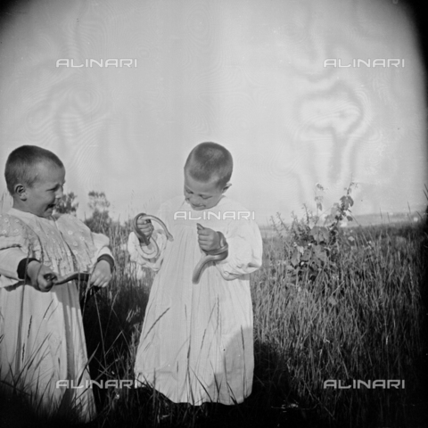 MFA-S-0SN398-000D - Portrait of two children in traditional clothes playing with some serpents in the countryside - Data dello scatto: 1900 ca. - Archivi Alinari, Firenze