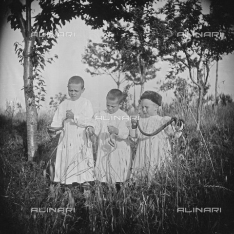 MFA-S-0SN399-000S - Three children in traditional clothes playing with some serpents in the countryside - Data dello scatto: 1900 ca. - Archivi Alinari, Firenze