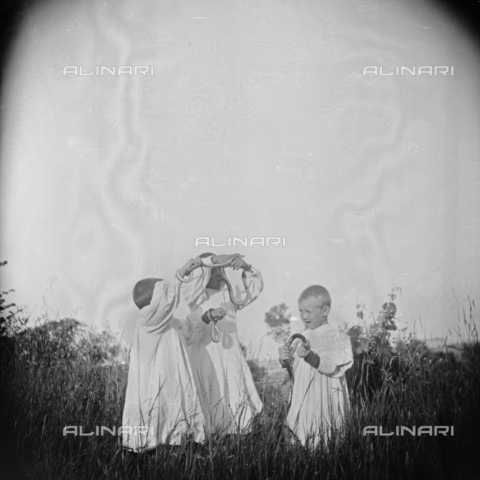 MFA-S-0SN400-000S - Three children in traditional clothes playing with some serpents in the countryside - Data dello scatto: 1900 ca. - Archivi Alinari, Firenze