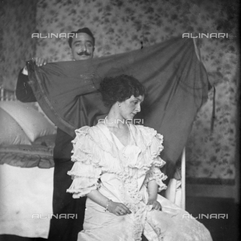 MFA-S-0SN410-000D - Portrait of Lina Cavalieri; behind her a man holding a sheet - Date of photography: 1909 - Alinari Archives-Michetti Archive, Florence