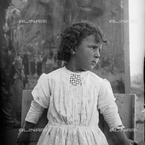MFA-S-0SN425-000D - Portrait of a little girl wearing a white dress in front of a picture - Data dello scatto: 1900 ca. - Archivi Alinari, Firenze