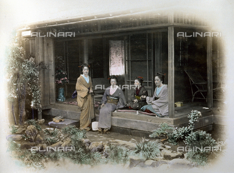 MFC-A-004626-0002 - Full-length portrait of four young geishas in traditional dress. Three of them are seated under the portico of a tea house while the fourth, standing, has a shyamisen on her left arm - Data dello scatto: 1863-1868 ca. - Archivi Alinari, Firenze