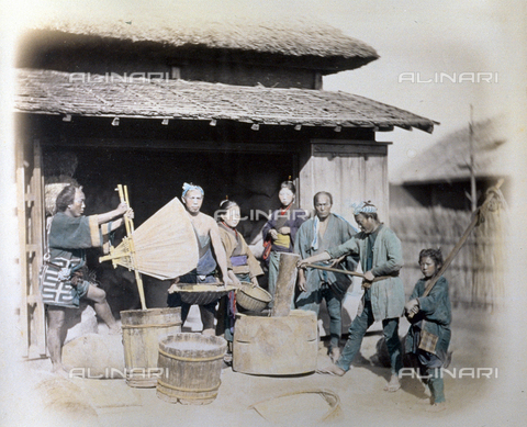 MFC-A-004626-0005 - Group of japanese men and women, in traditional humble clothing, cleaning rice on the threshold of a warehouse - Data dello scatto: 1863-1868 ca. - Archivi Alinari, Firenze